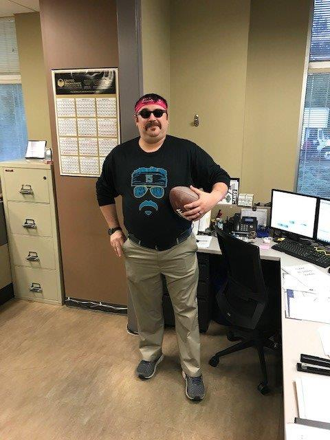 Employee in Charlotte office dressed up for Halloween with sunglasses and a football
