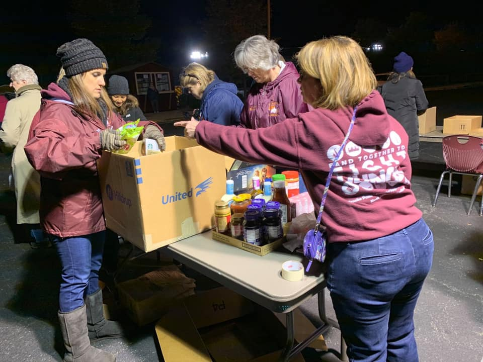 Volunteers organize food donations into Hilldrup moving boxes