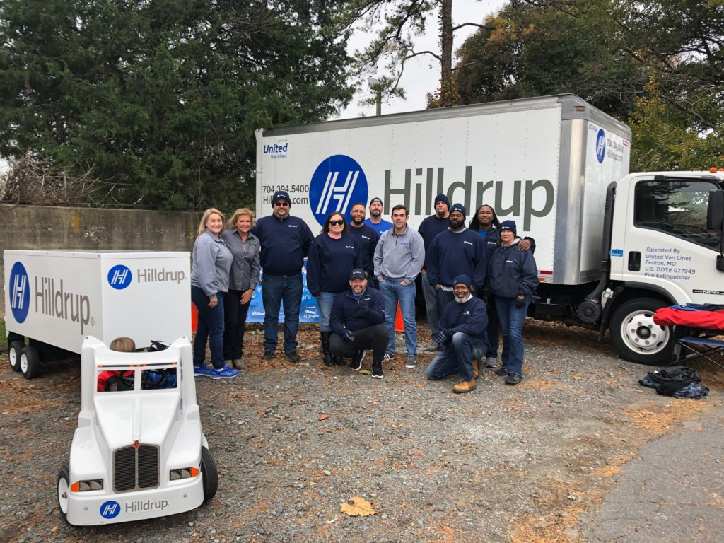 Hilldrup office employees and service team members gather for a photo next to a Hilldrup truck..