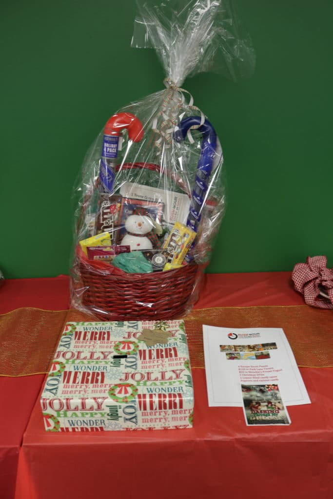 Christmas basket with gift cards and lottery tickets on table