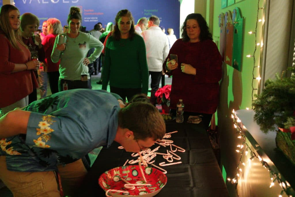 Hilldrup employee plays a Minute to Win It game with candy canes during Christmas party.
