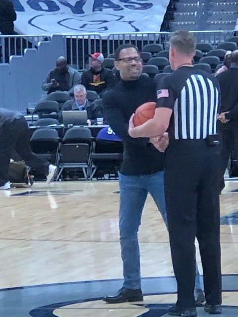 Remus presents the game ball to the ref during the Georgetown game.