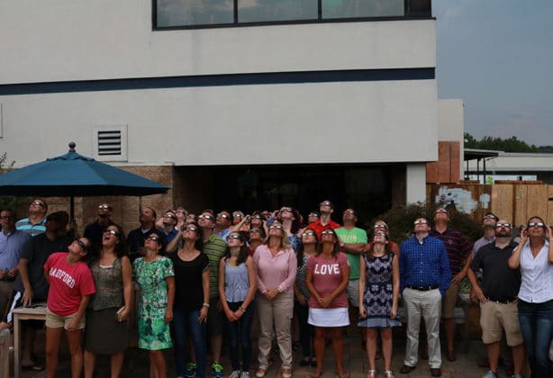 Hilldrup employees watching the solar eclipse in August 2017 with their solar eclipse glasses to protect their eyes