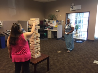 Hilldrup Orlando branch employees playing life-size Jenga during a Wednesday Wake-Up morning activity