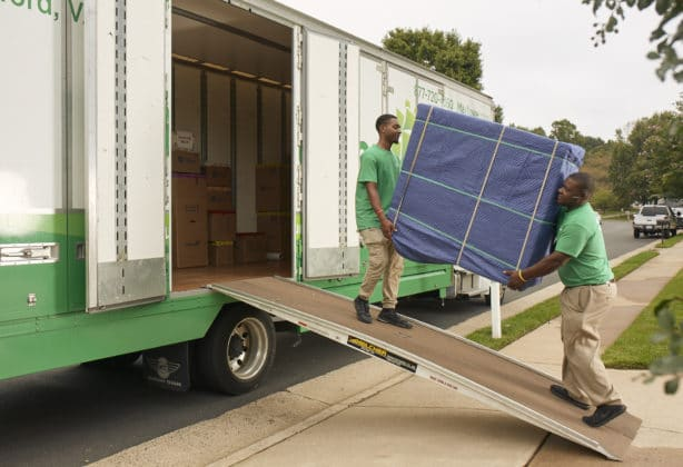 Two guys moving furniture onto a truck