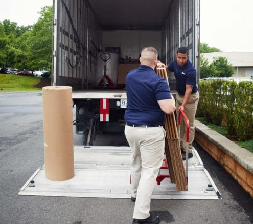 Two movers use a lift gate to put items into a truck