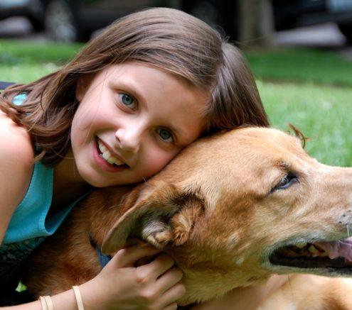 Young girl embracing pet dog.