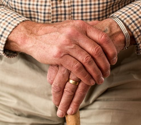 Elderly man's hands holding a cane.