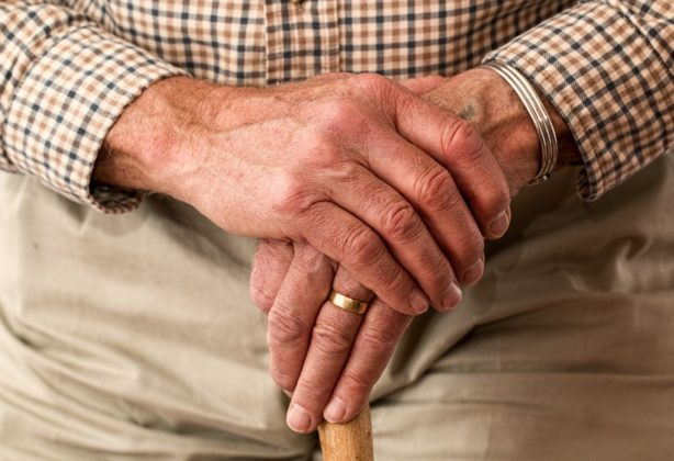 Elderly man's hands holding a cane.