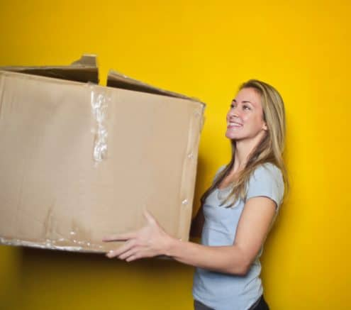 Young woman holding a moving box.|Young woman holding moving box.