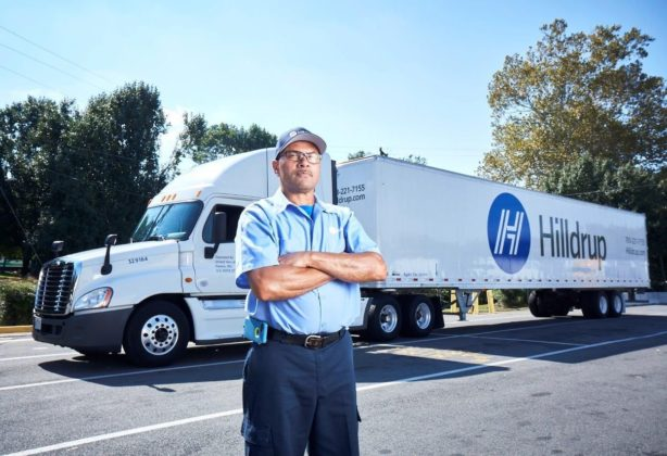 Fred Minor, Hilldrup Van Operator, stands besides a Hilldrup tractor trailer.
