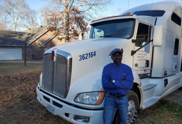 Olu, Stafford Van Operator, stands by his truck.