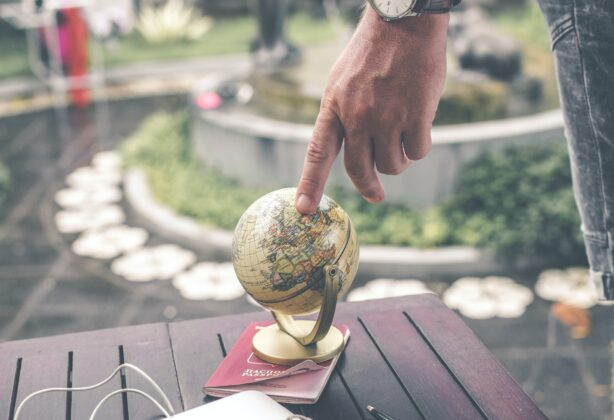 Person touching small globe on top of a passport.