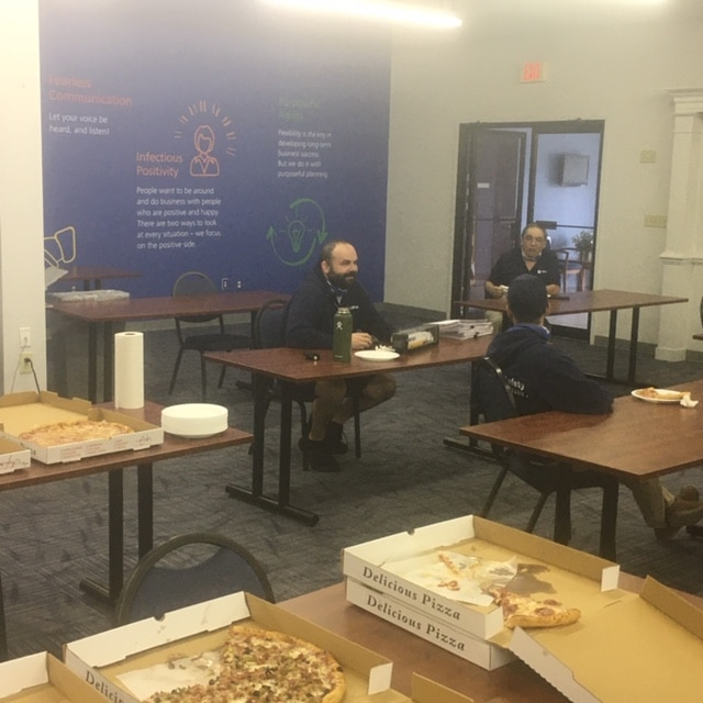 William Johnson enjoys a pizza party with colleagues at Hilldrup's Stafford office as part of his goodbye party.