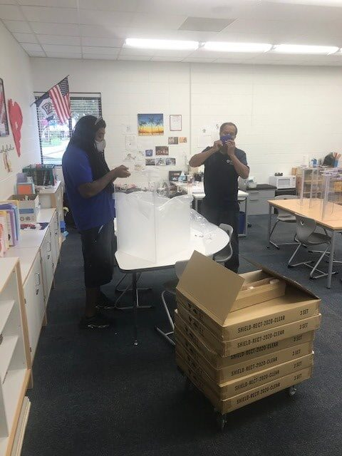 Hilldrup Charlotte's team assists with installing plexiglass shields in a classroom.