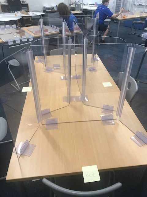 Plexiglass shields are displayed on students' desks in a classroom.