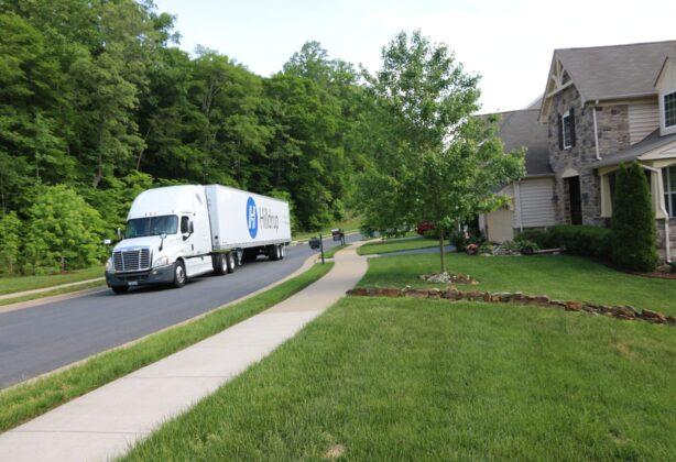 Hilldrup truck driving through a residential neighborhood.