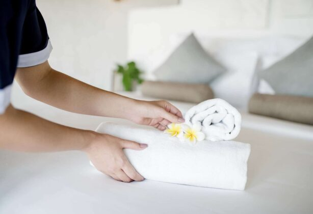 Hotel staff member placed some towels and items for guests on a bed.