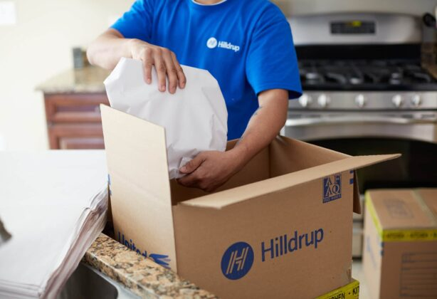 Hilldrup employee packing wrapped items in a kitchen.