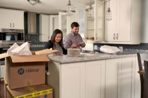 Couple unpacking items in their kitchen.