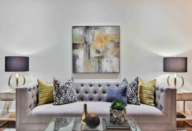 Picture of a living room with a couch, coffee table, side tables, lamps and a painting.