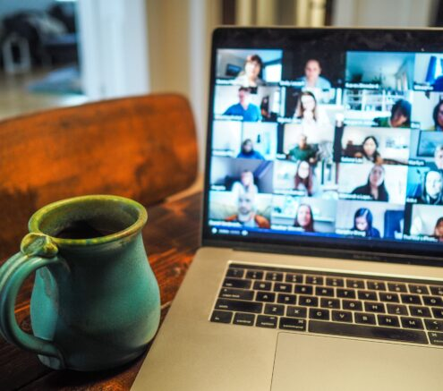 Picture of a desk with a coffee mug and a laptop with a Zoom screen up.