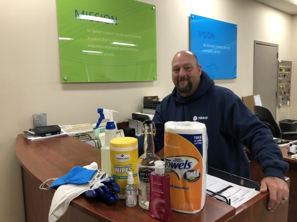 Hilldrup Operations employee with cleaning supplies at the office