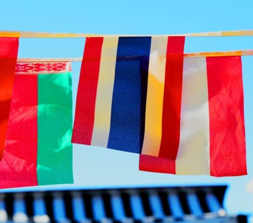 Different international flags hanging against a blue sky.