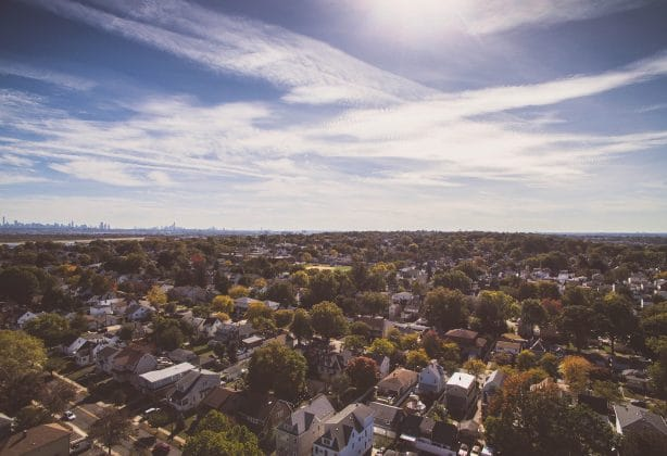 Overhead shot of neighborhood with blue sky and clouds in the background.