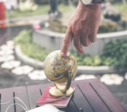 Person touching a small globe that is sitting on a table.