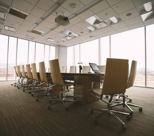 Conference room with a large table and chairs against a wall of windows.