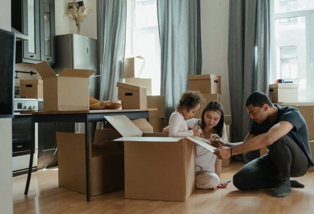Two adults and one small child gathered around moving boxes in a kitchen.